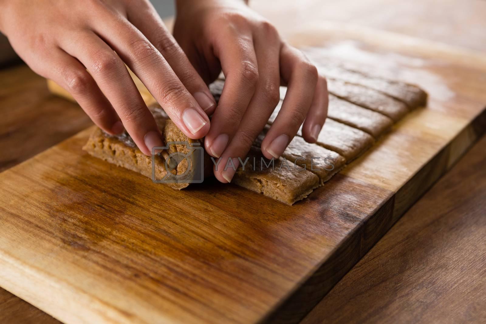 Woman arranging dough on chopping board by Wavebreakmedia