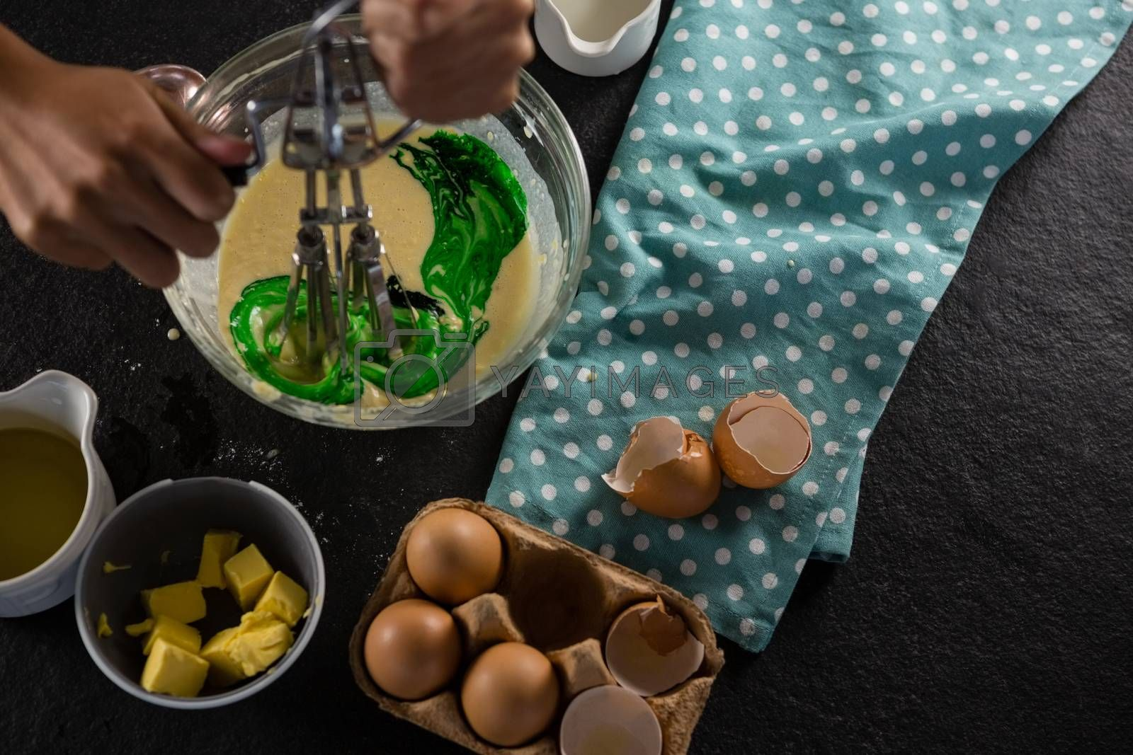 Woman whisking batter after adding green food color by Wavebreakmedia