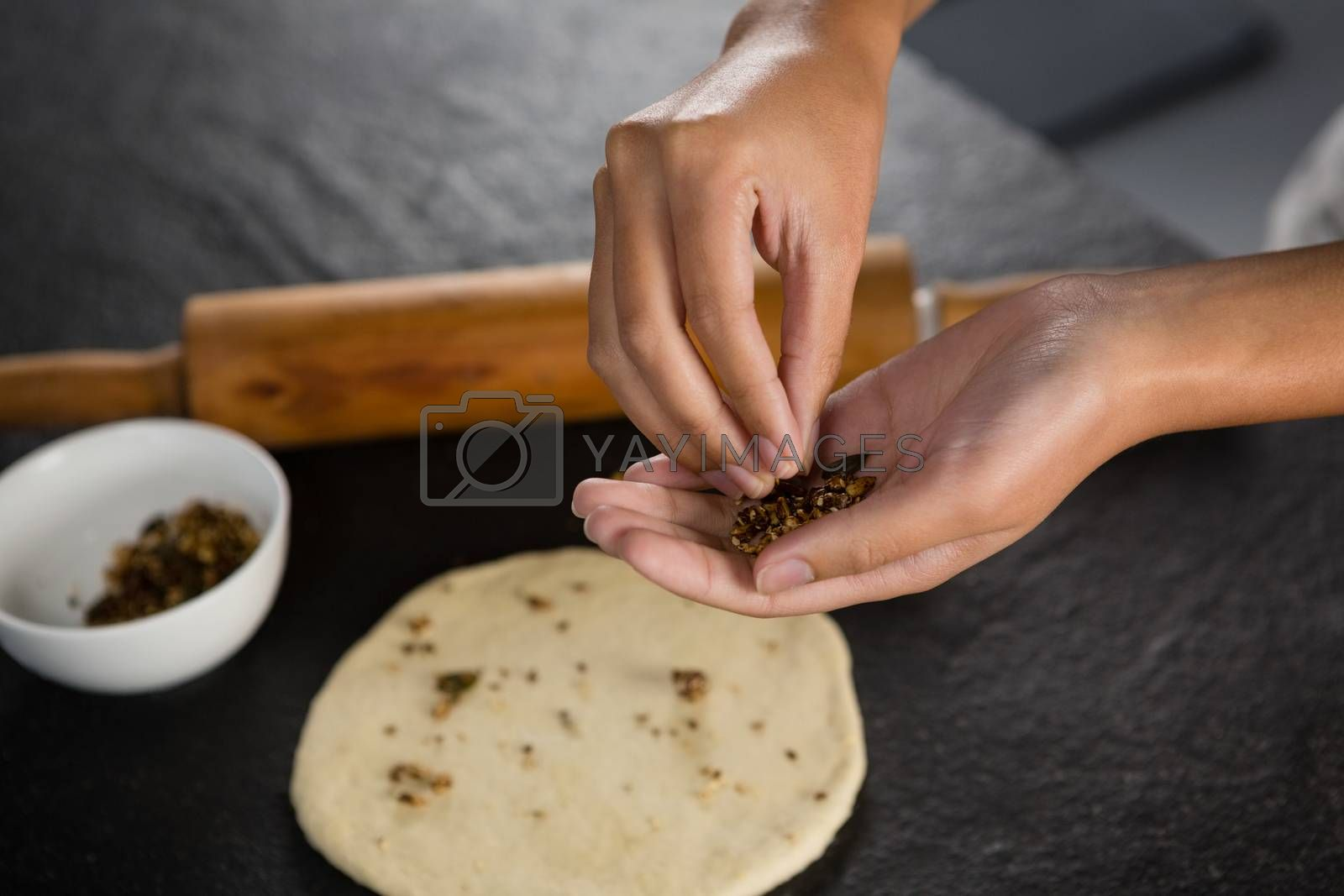 Woman adding dry fruits over flattened dough by Wavebreakmedia