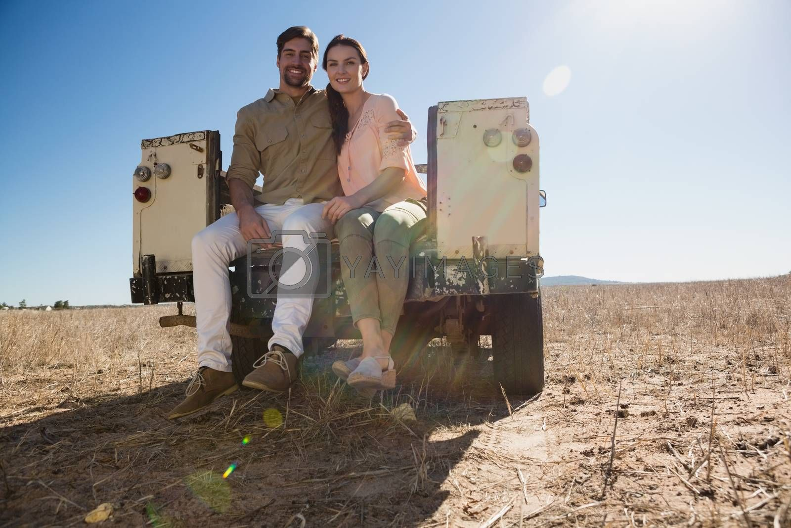 Full length portrait of couple sitting in off road vehicle on landscape by Wavebreakmedia