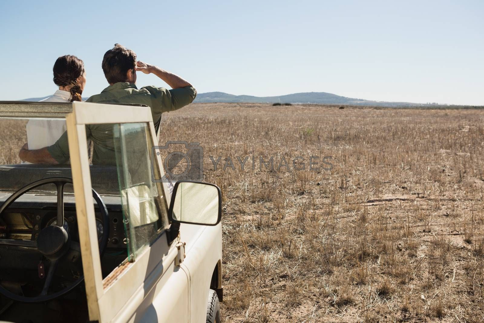 Rear view of couple on off road vehicle looking at landscape by Wavebreakmedia