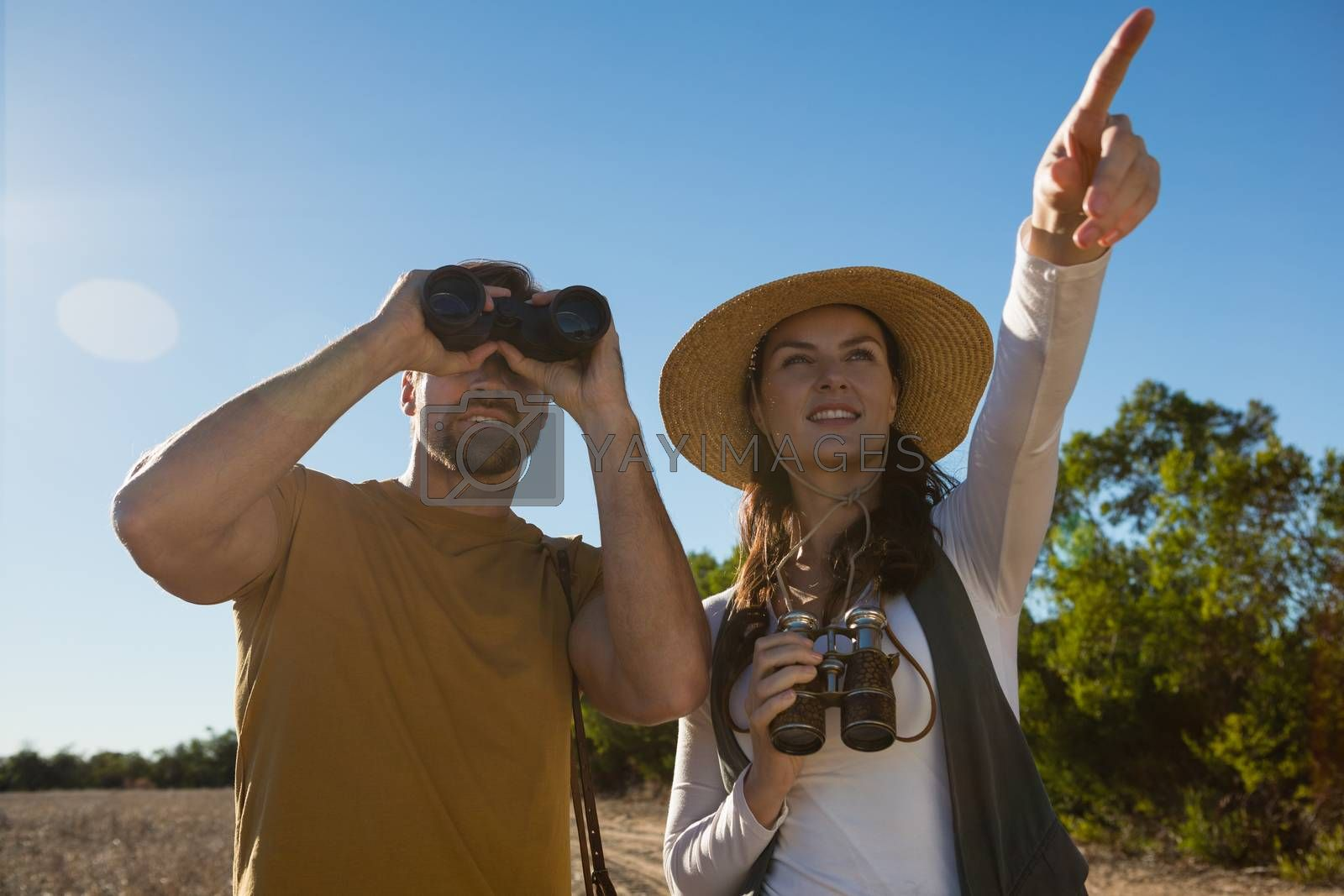 Young couple with binoculars at forest by Wavebreakmedia