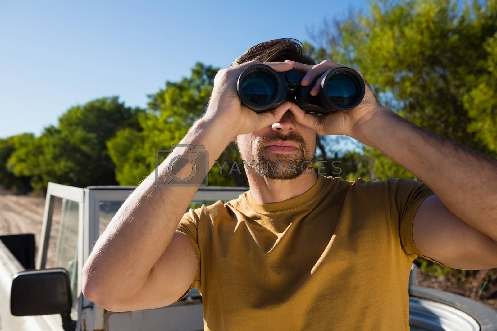 Man looking through binocular by Wavebreakmedia