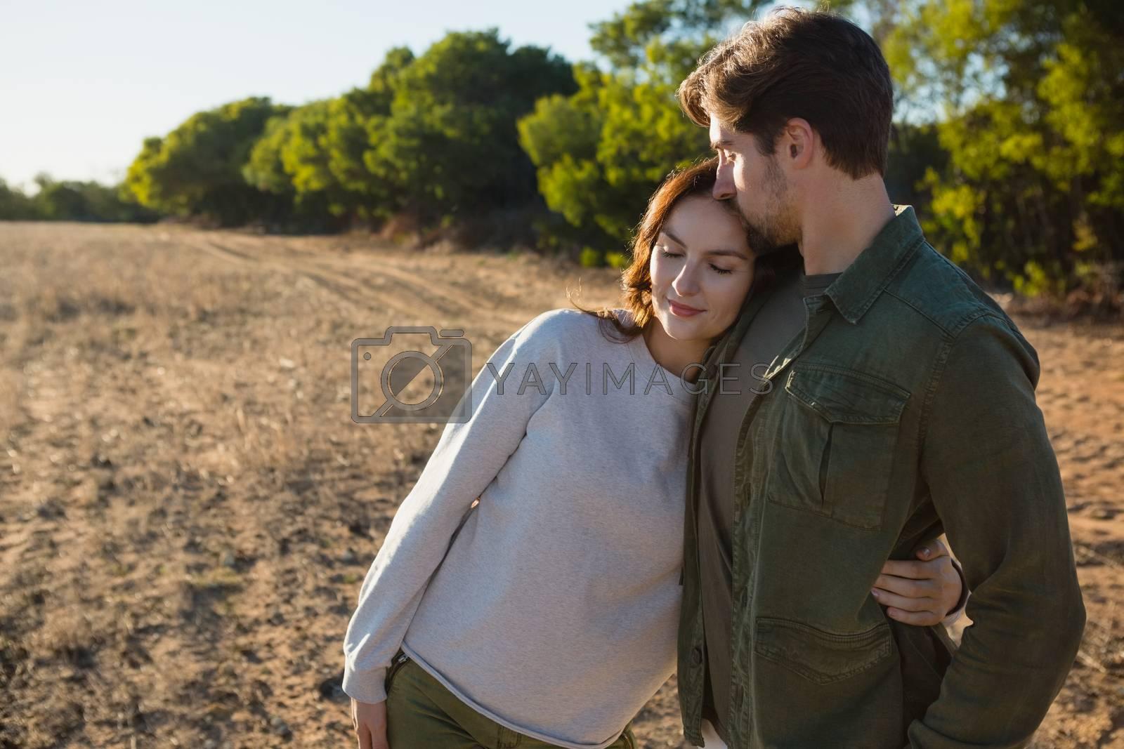 Romantic couple on field by Wavebreakmedia
