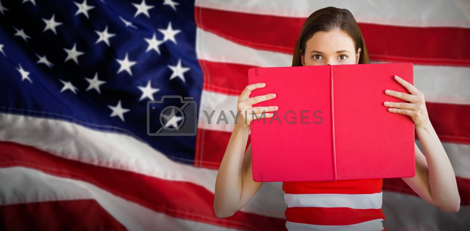 Composite image of student holding book over face by Wavebreakmedia