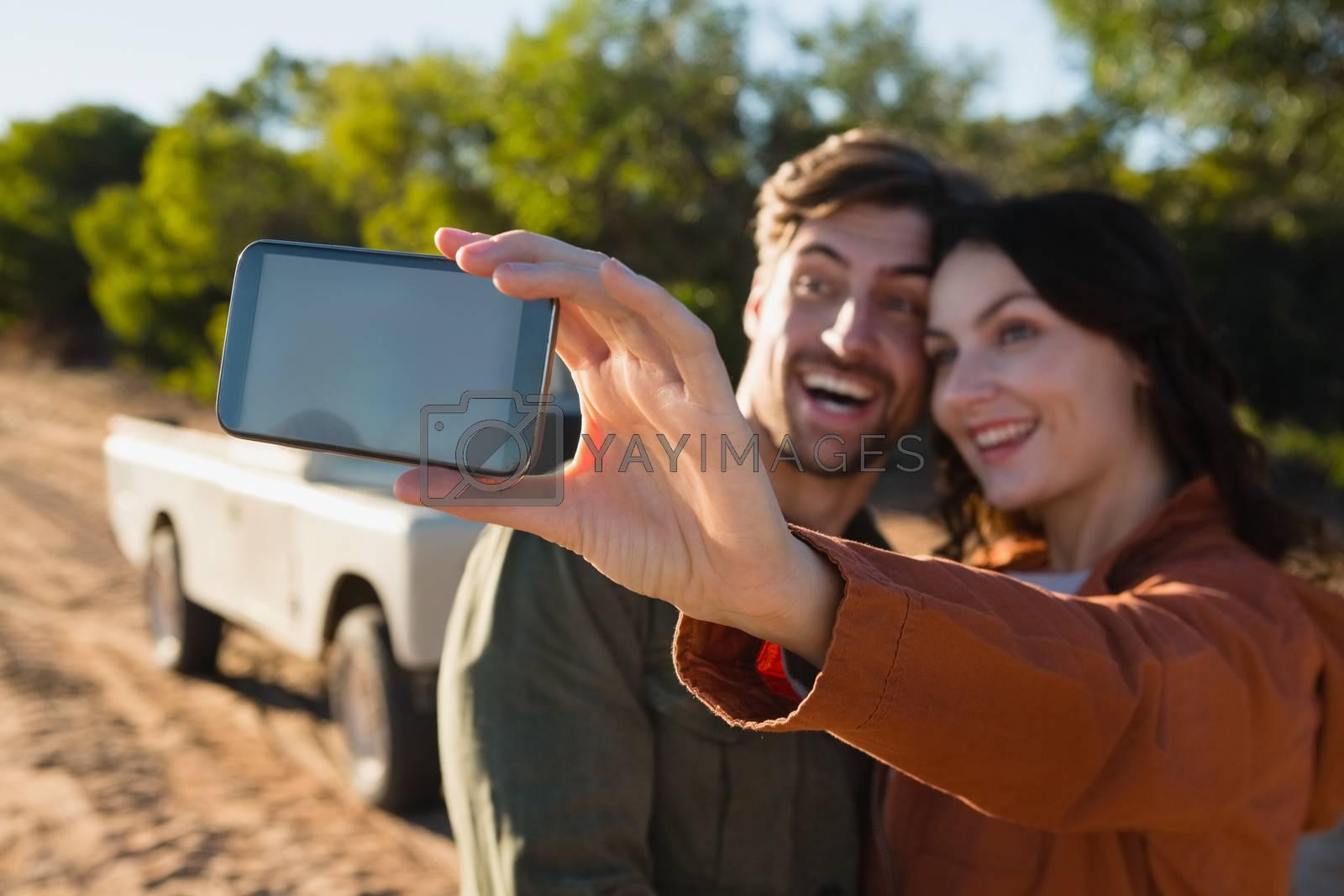 Happy woman taking selfie with man by Wavebreakmedia