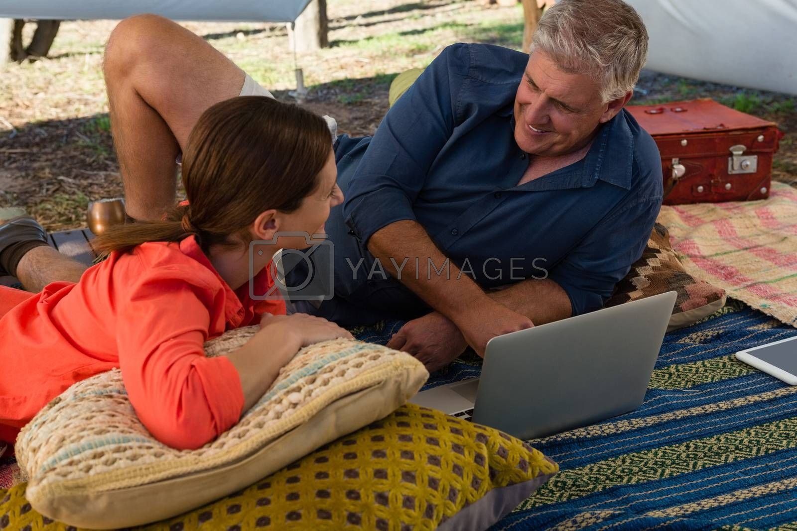 Man with woman using laptop in tent by Wavebreakmedia