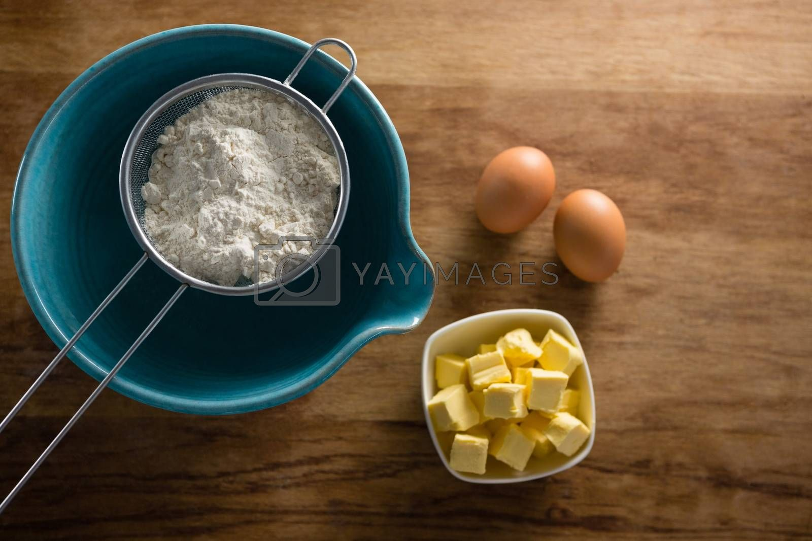 Flour in stainer with eggs and cheese by Wavebreakmedia