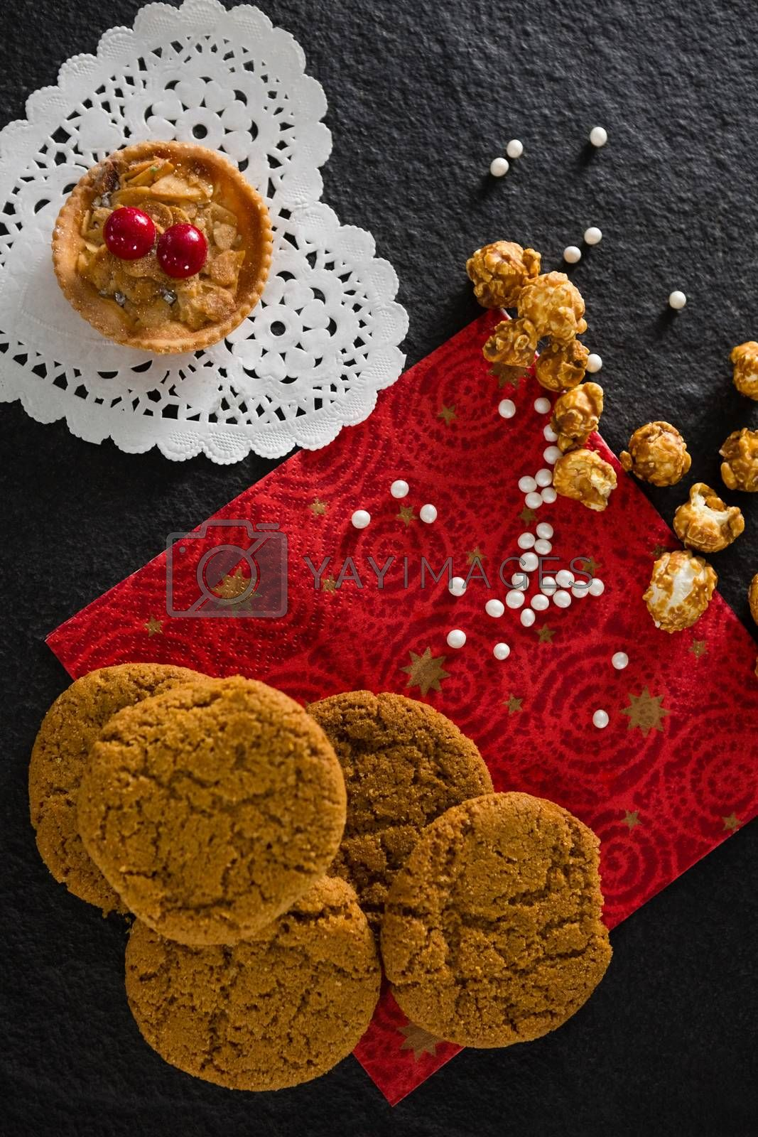 Tart and cookies with pearls on red place mat by Wavebreakmedia