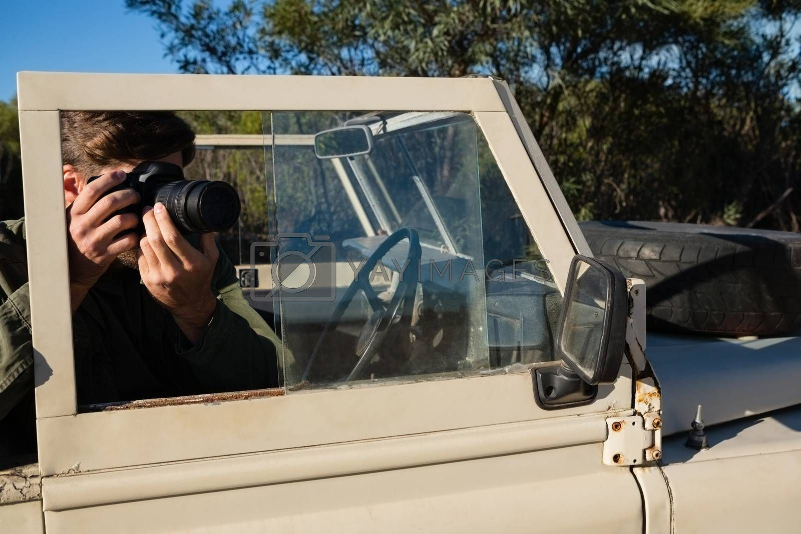 Man photographing while sitting in off road vehicle by Wavebreakmedia