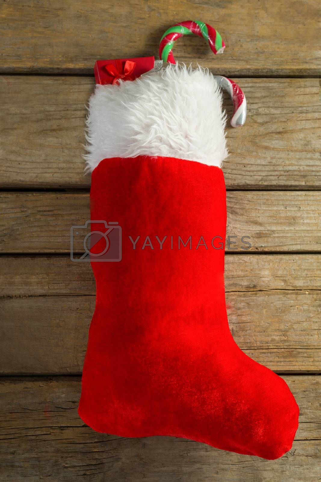 Wrapped gift box and candy cane in stocking against wooden wall by Wavebreakmedia