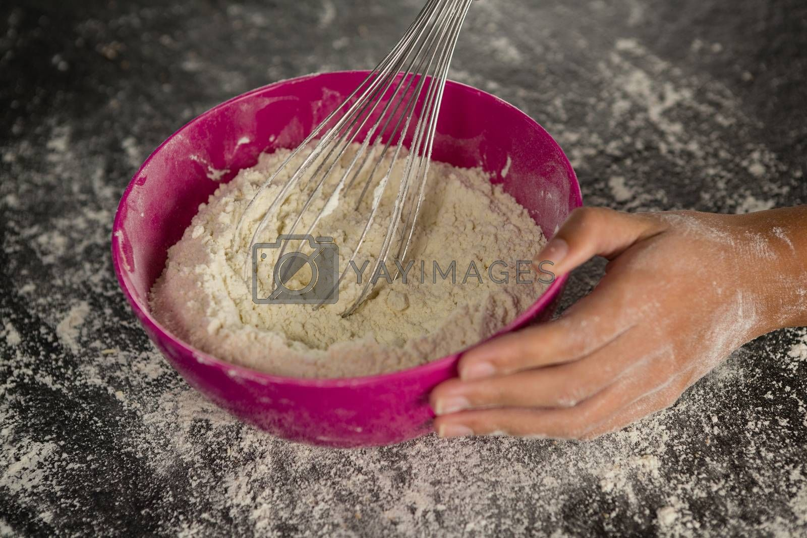 Woman whisking flour in bowl by Wavebreakmedia
