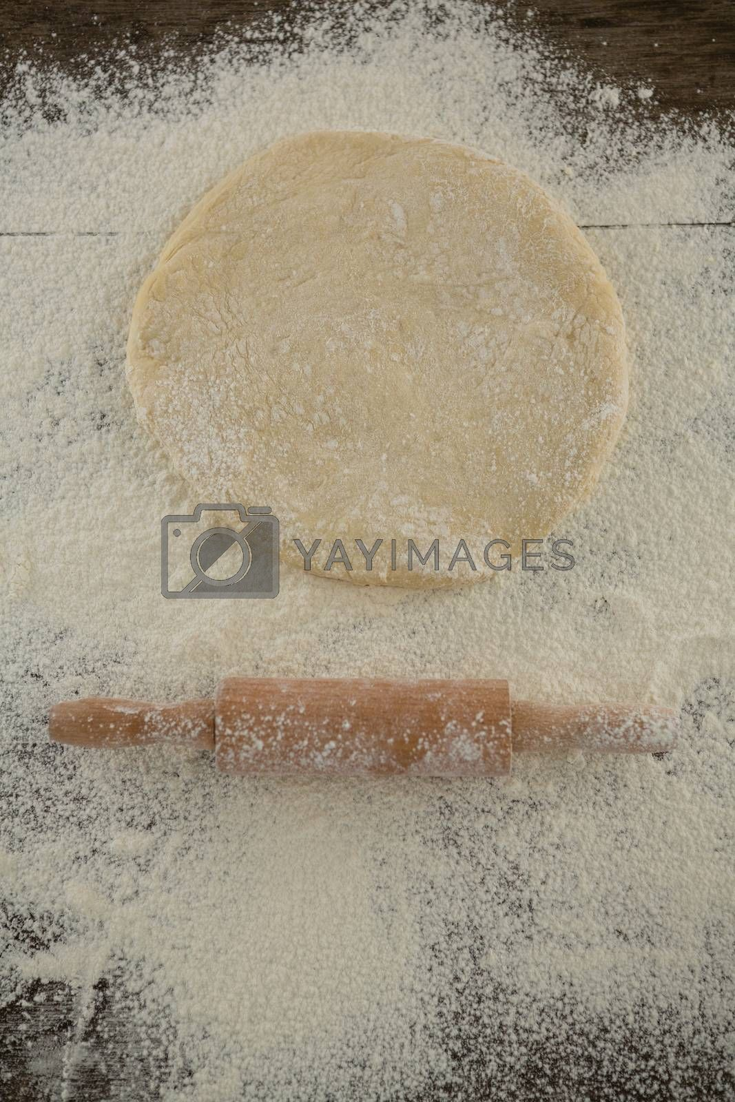 Flattened dough sprinkled with flour on a wooden table by Wavebreakmedia