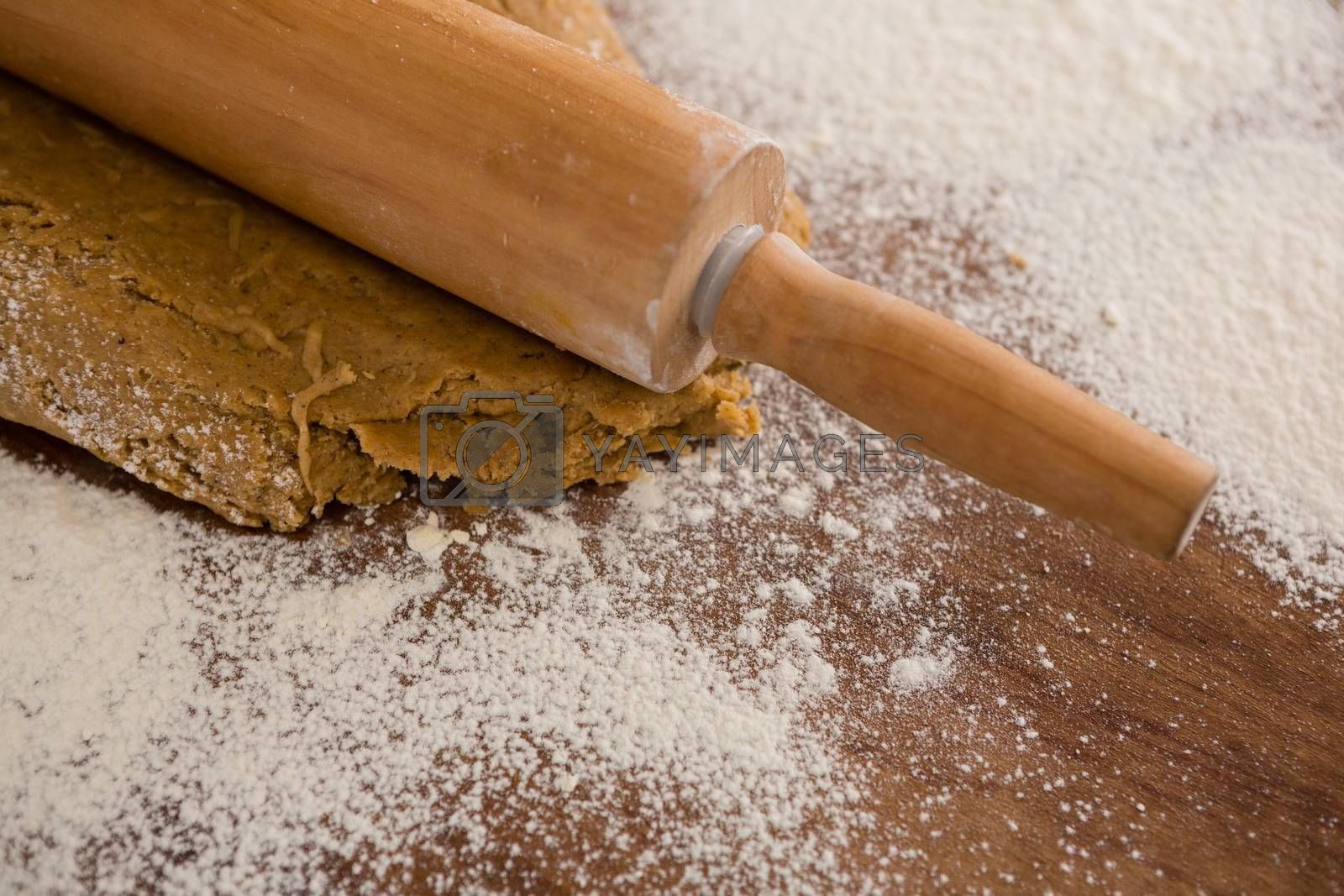 Flattening dough with rolling pin with sprinkled over flour on a wooden table by Wavebreakmedia
