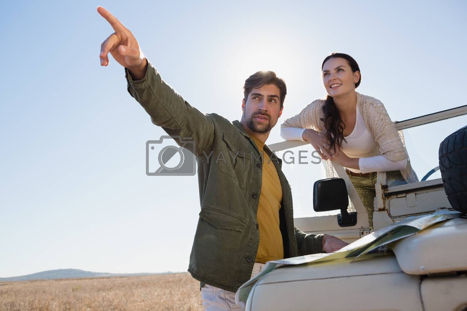Man with woman pointing by off road vehicle by Wavebreakmedia