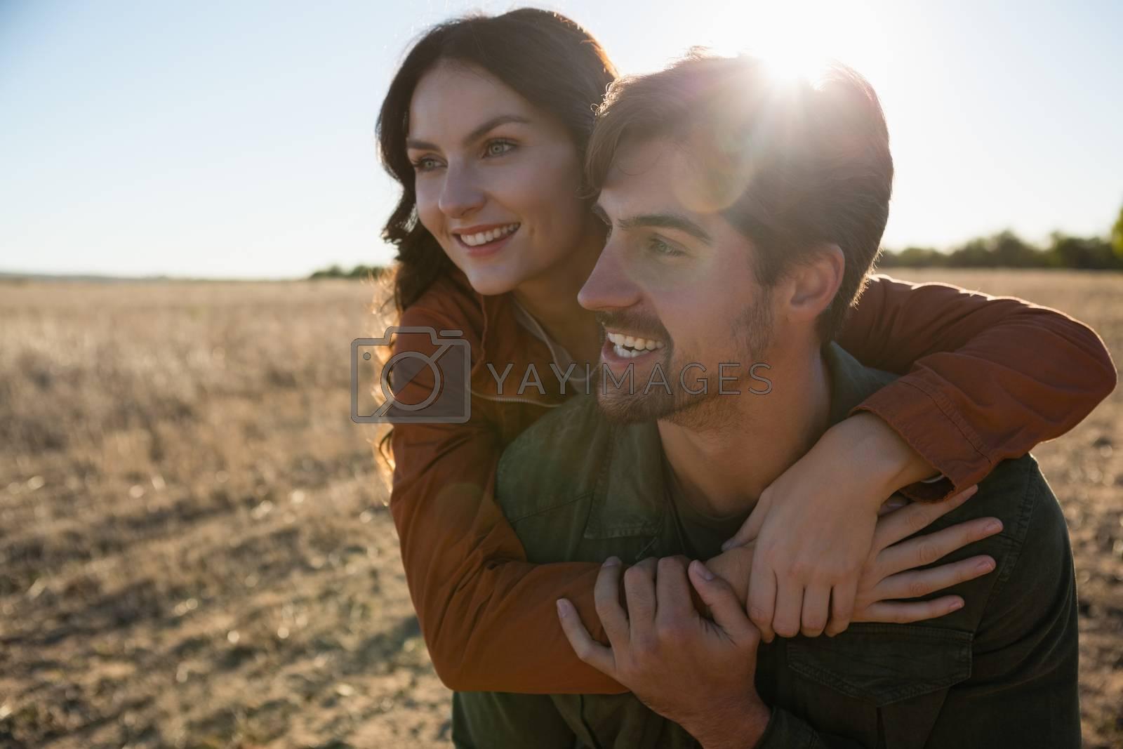 Man giving woman piggyback ride on landscape by Wavebreakmedia