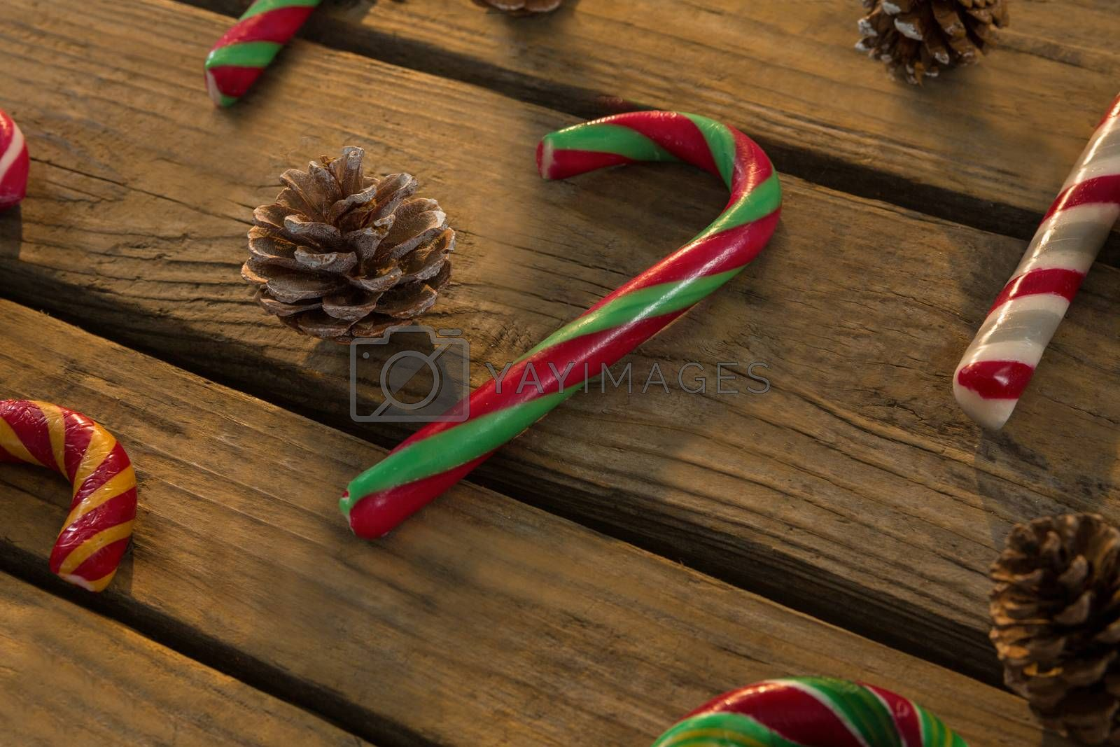 High angle view of candy canes and pine cones on table by Wavebreakmedia