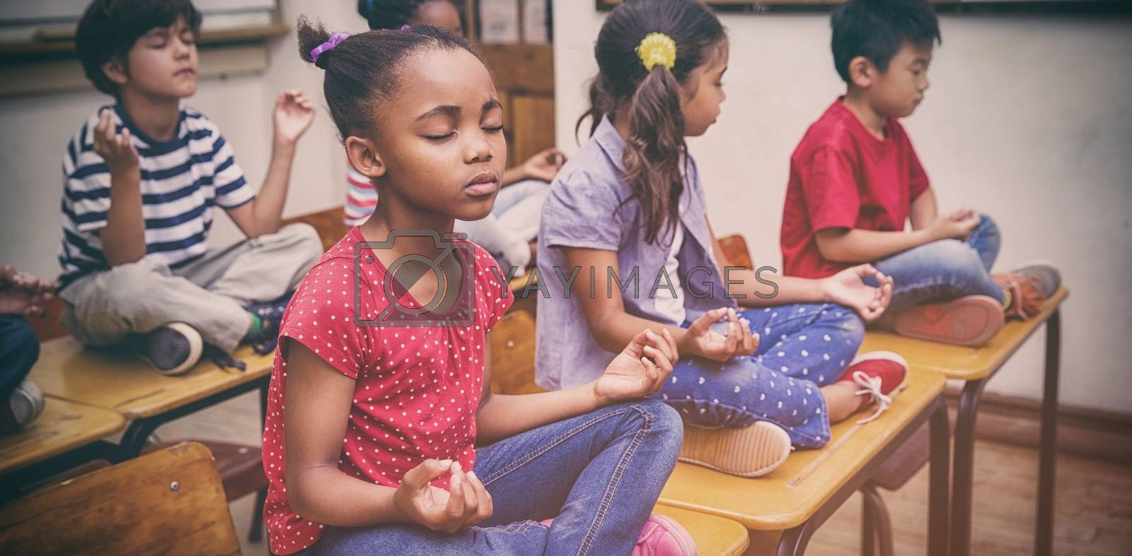 Pupils meditating in lotus position on desk in classroom by Wavebreakmedia