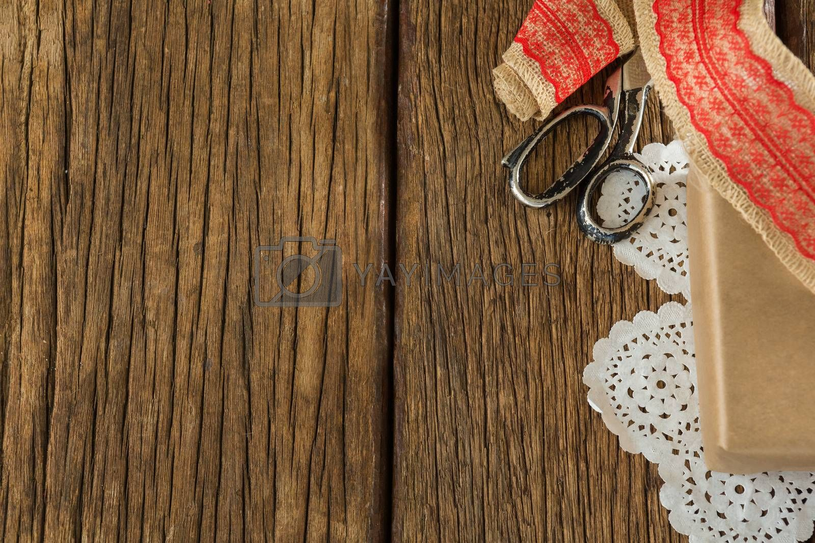 Wrapped gift, ribbon and scissors on wooden plank by Wavebreakmedia