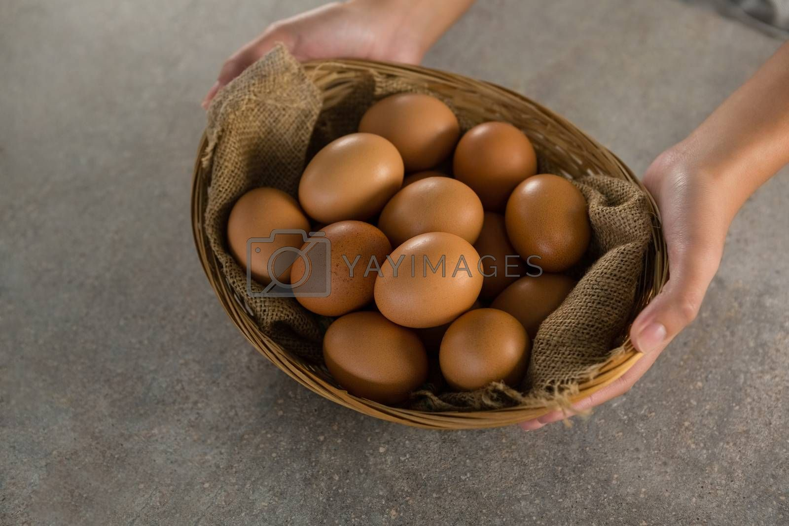 Woman holding basket with brown eggs by Wavebreakmedia