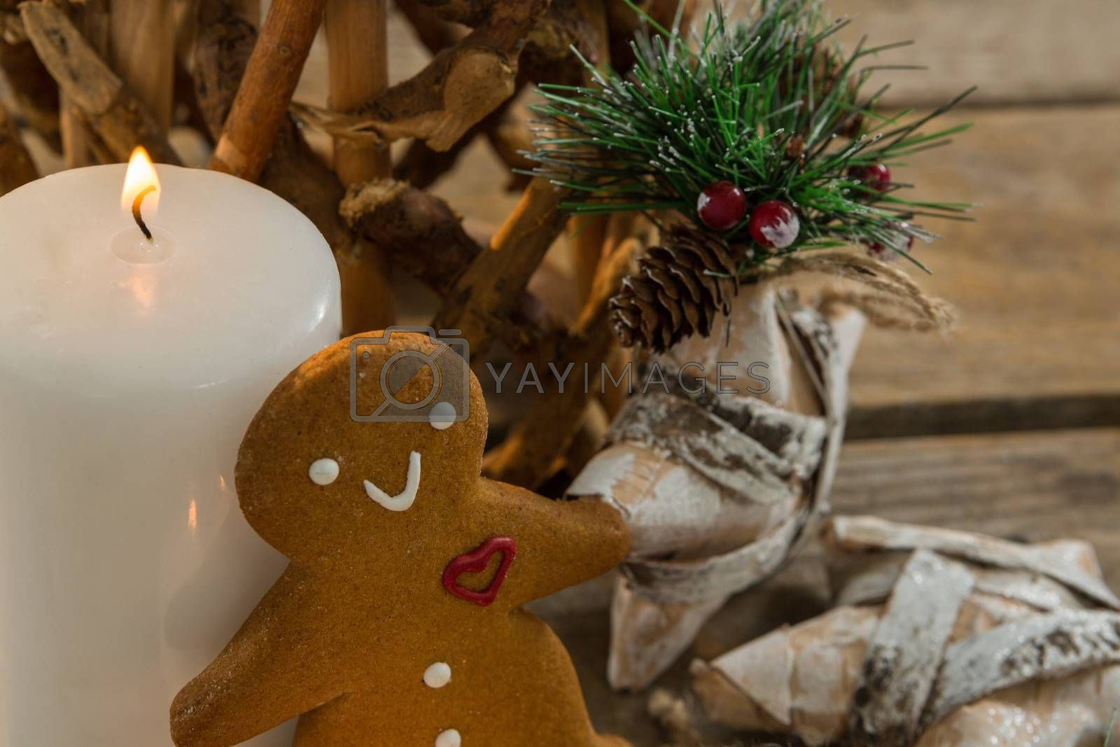 Gingerbread cookie by illuminated candle and star shape decorating by Wavebreakmedia