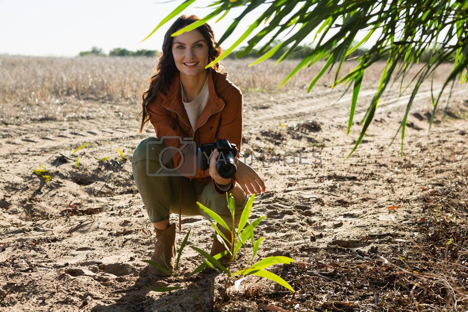 Portrait of woman with camera on field by Wavebreakmedia