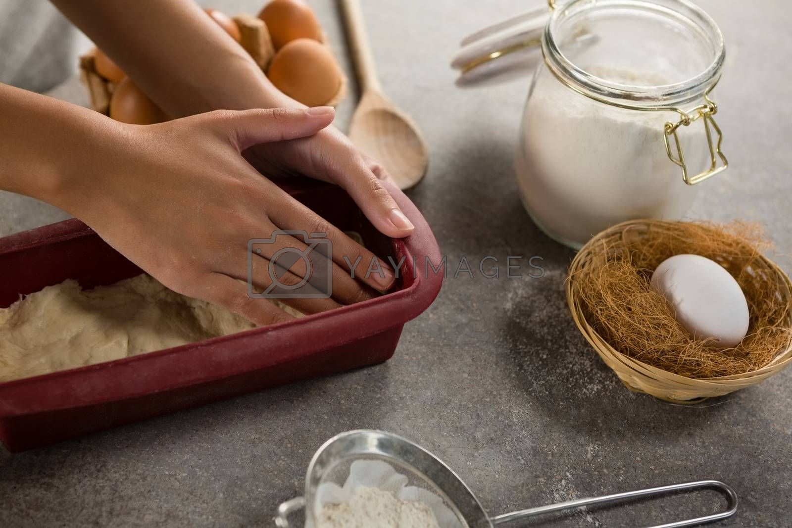 Woman preparing dough surrounded with various ingredients by Wavebreakmedia