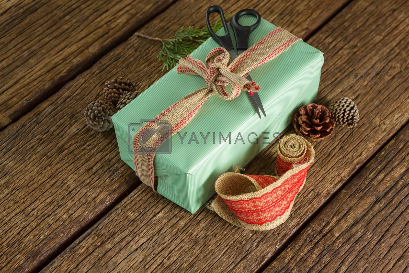 Scissors, pine cones, leaves and ribbon with wrapped gift box on wooden table by Wavebreakmedia