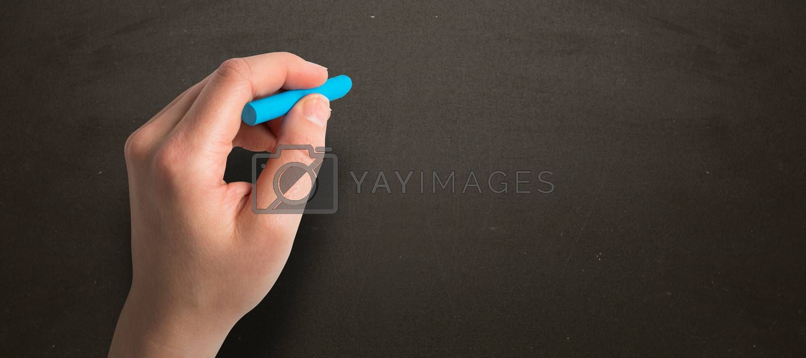 Composite image of hand holding blue chalk by Wavebreakmedia