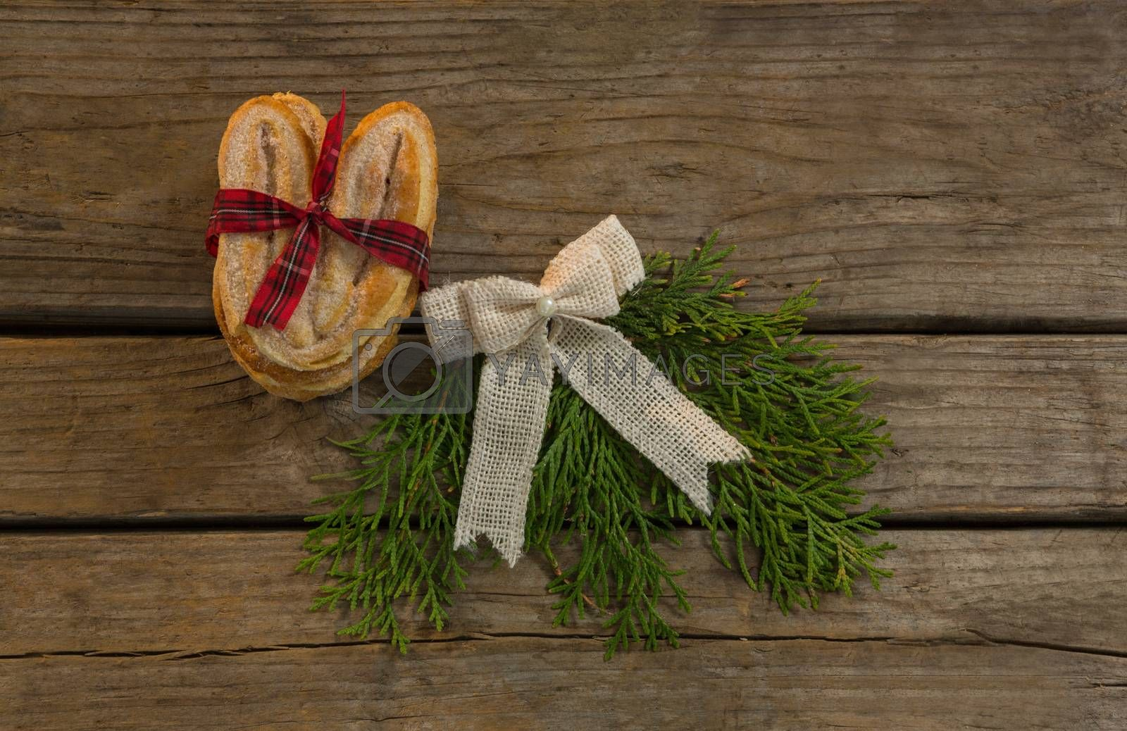 Overhead view sweet food with tied bow and pine needles on table by Wavebreakmedia