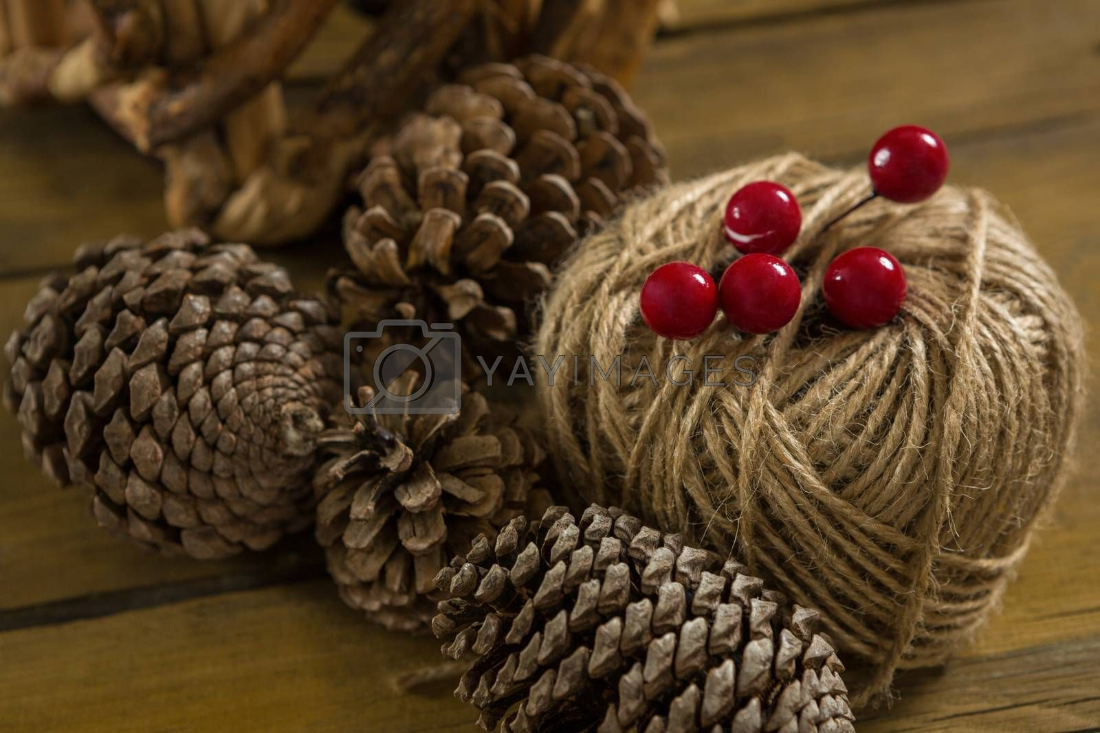 High angle view of pine cones with thread spool with push pin by Wavebreakmedia