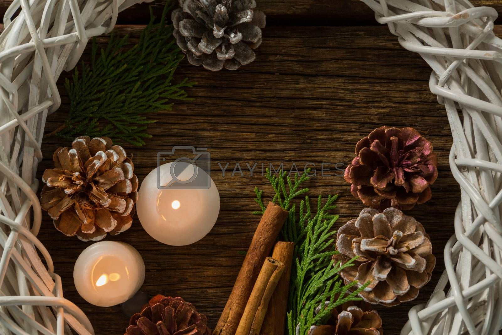 Directly above shot of pine cones with illuminated candles and wreath by Wavebreakmedia