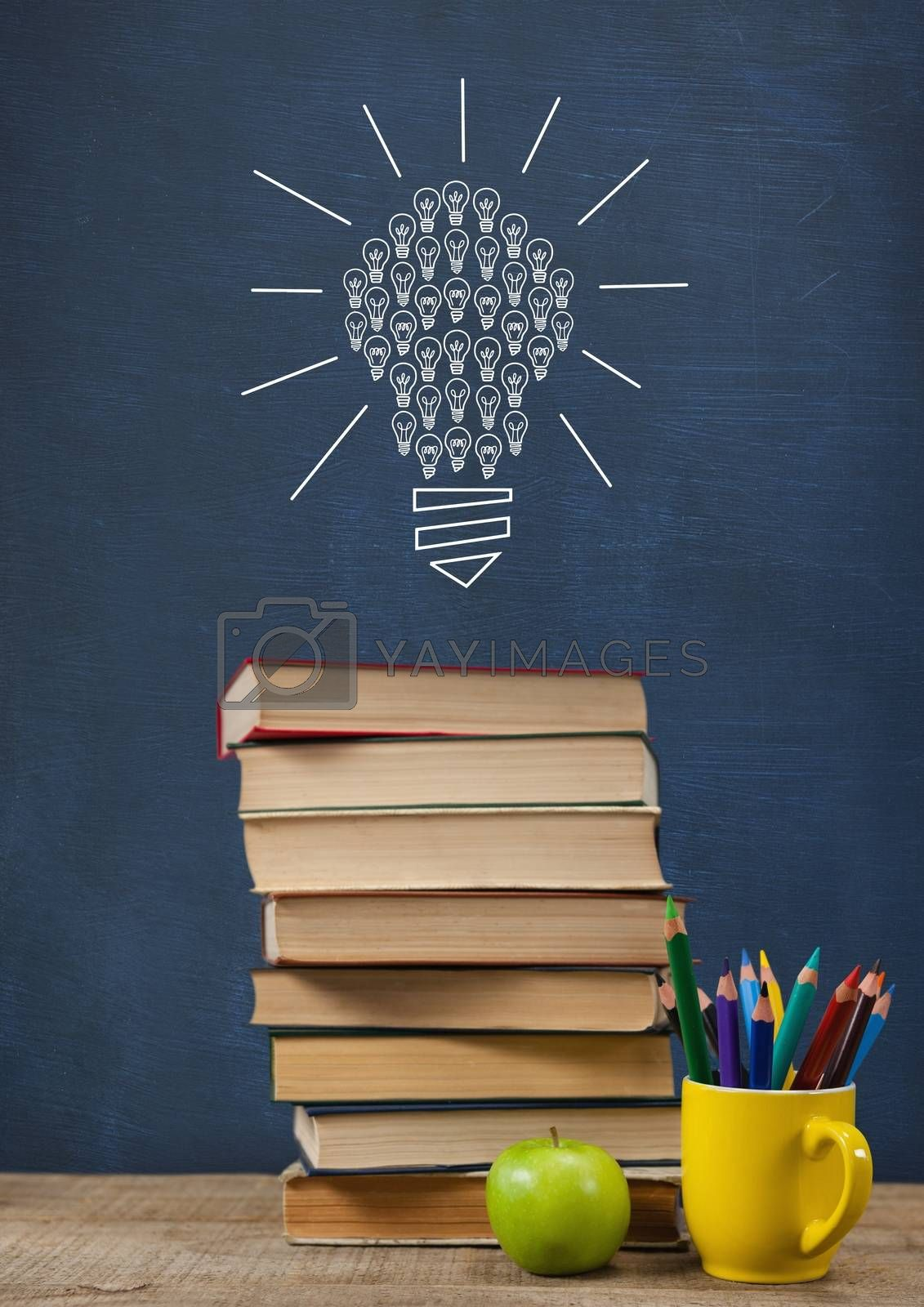 Books on the table against blue blackboard with bulb graphic by Wavebreakmedia