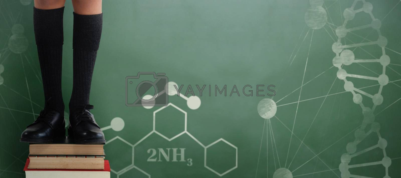 Composite image of low section of schoolboy standing on books by Wavebreakmedia