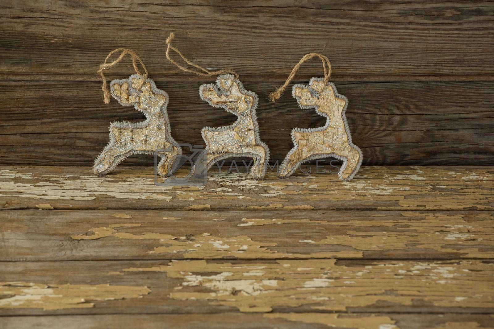 Reindeer decorations against wooden plank by Wavebreakmedia