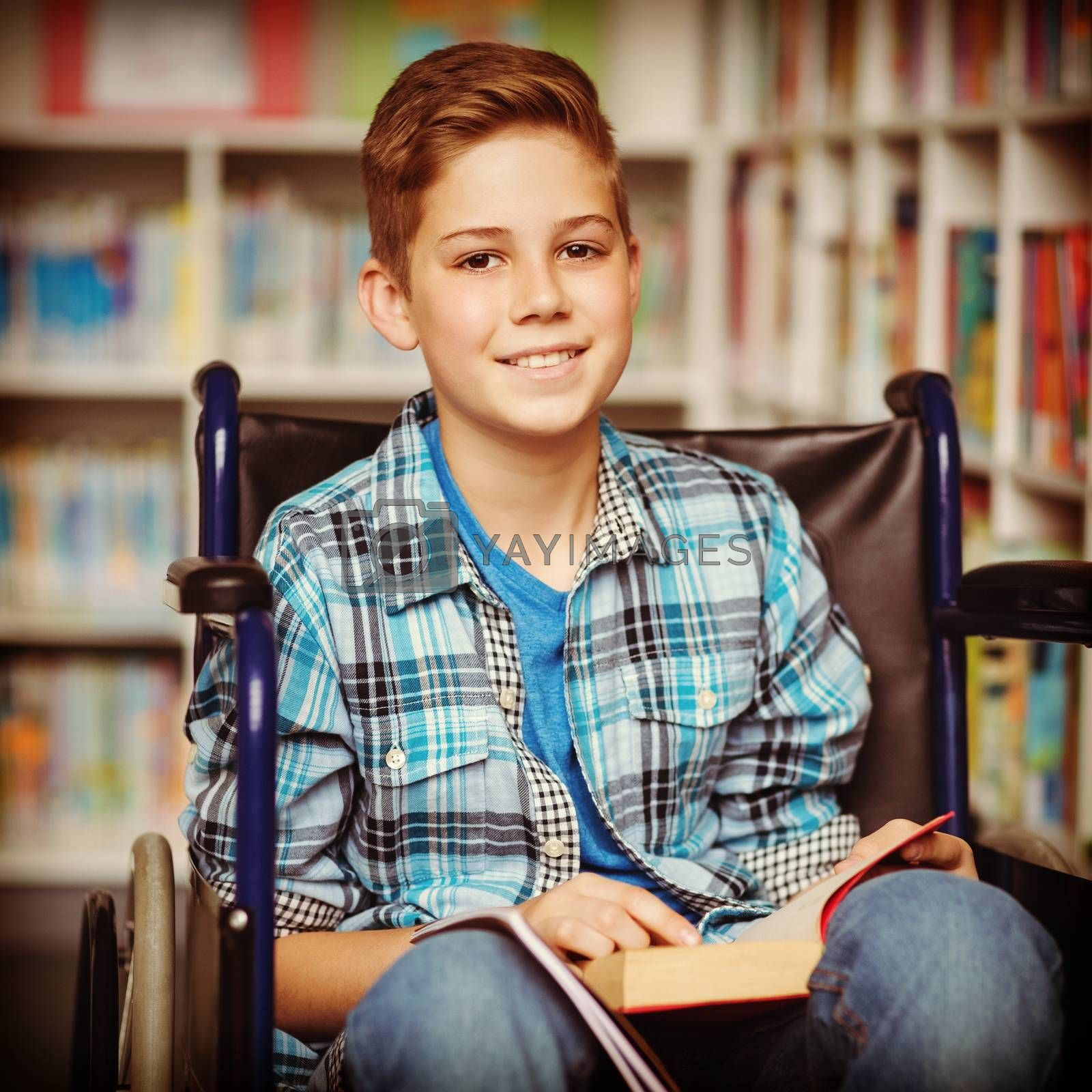 Portrait of disabled schoolboy holding book in library by Wavebreakmedia