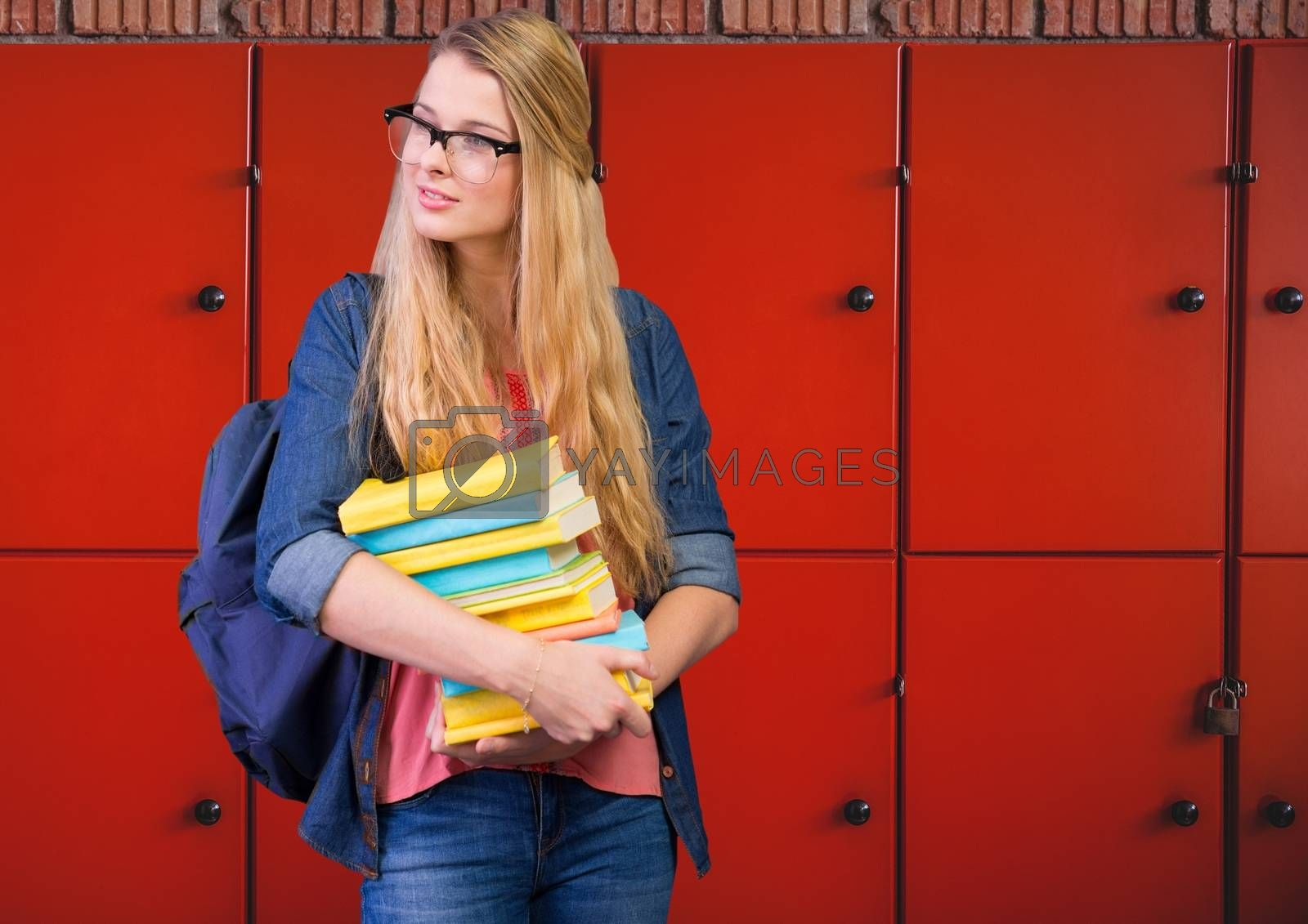 male student holding books in front of lockers by Wavebreakmedia