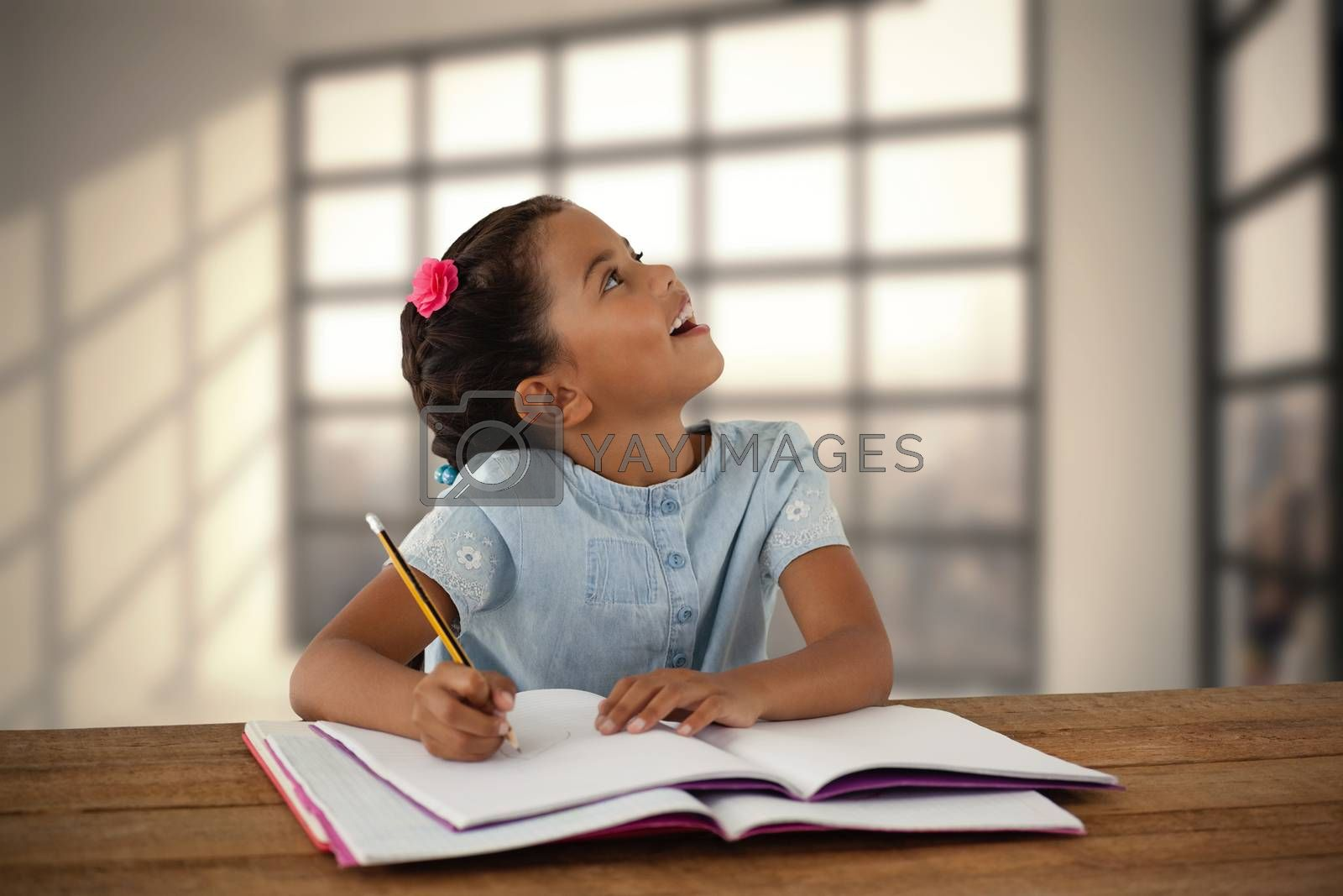 Composite image of girl looking up while writing in book by Wavebreakmedia