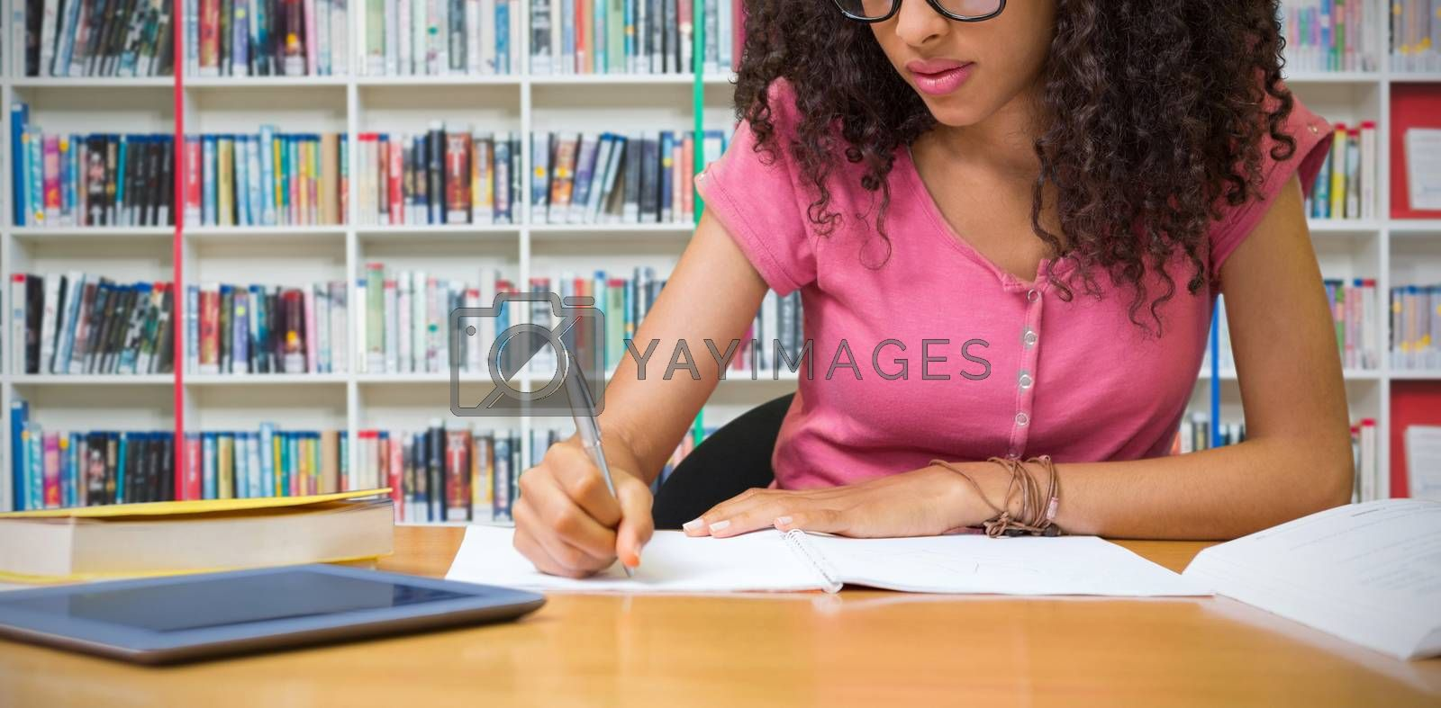 Composite image of student sitting in library writing by Wavebreakmedia