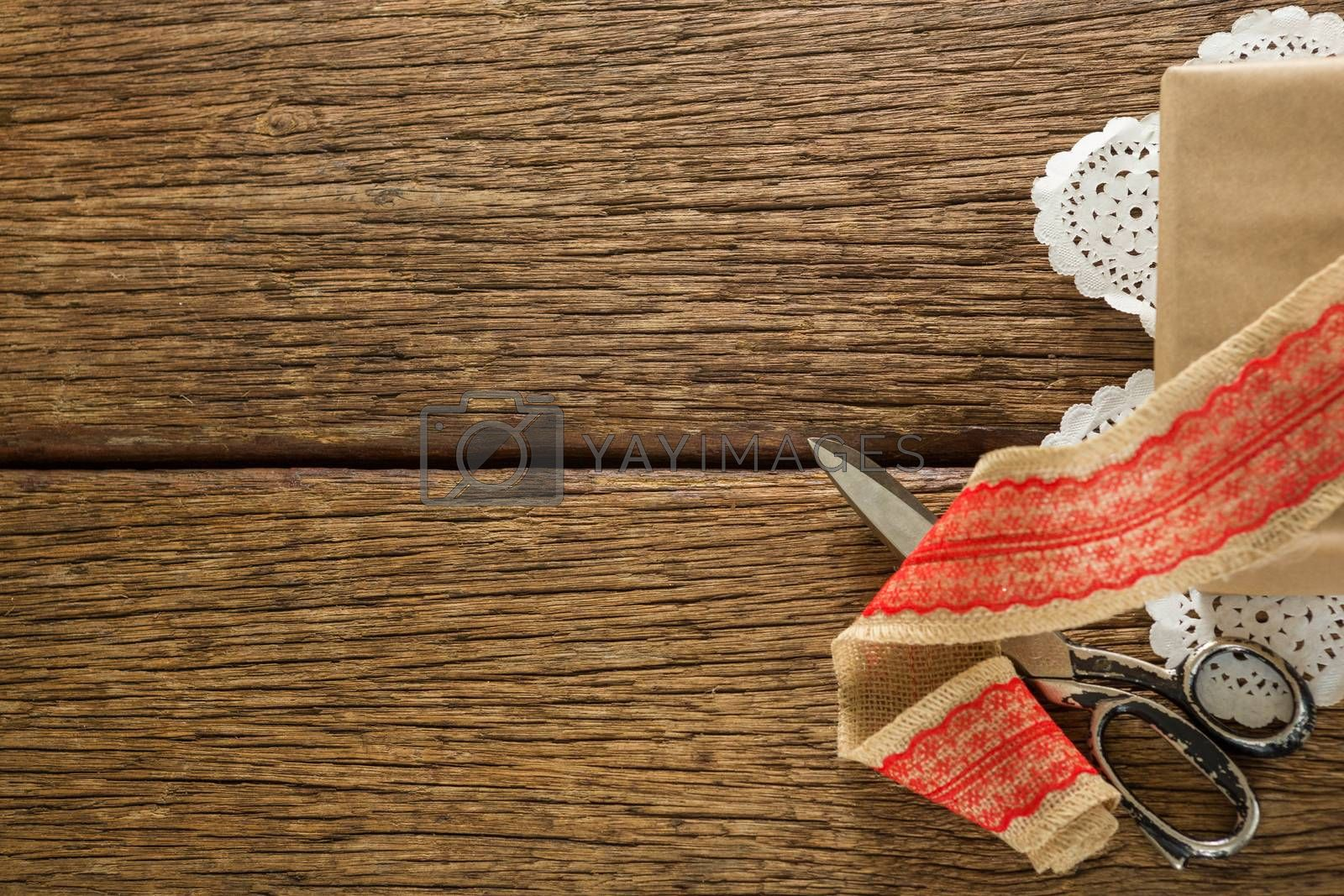 Ribbon and scissors on wooden plank by Wavebreakmedia