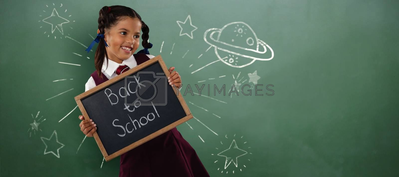 Composite image of smiling schoolgirl holding writing slate  by Wavebreakmedia