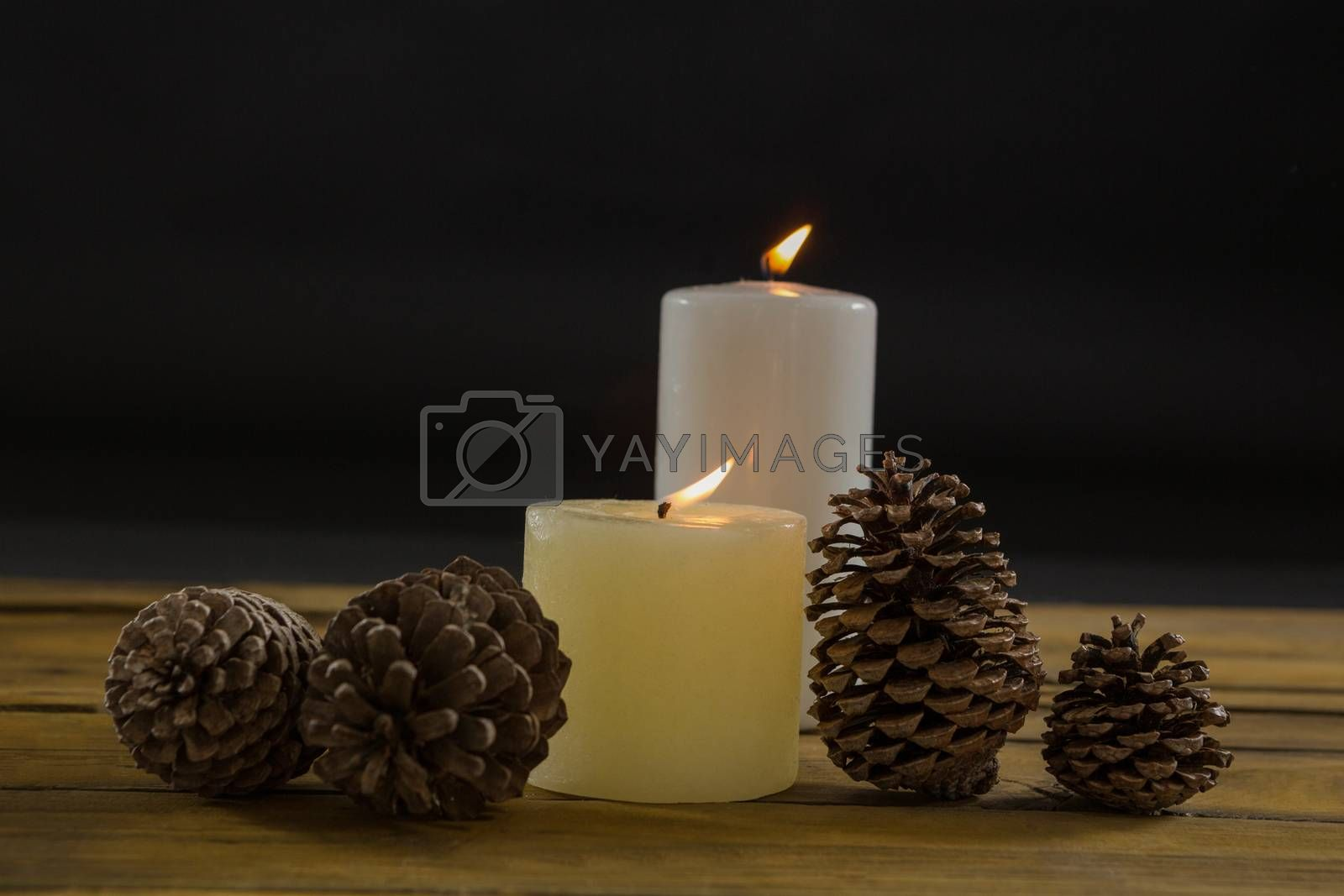 Close up of pine cones with illuminated candles on table by Wavebreakmedia