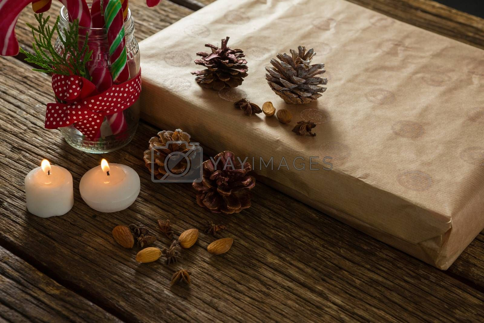 High angle view of illuminated candles with pine cones and gift box by Wavebreakmedia