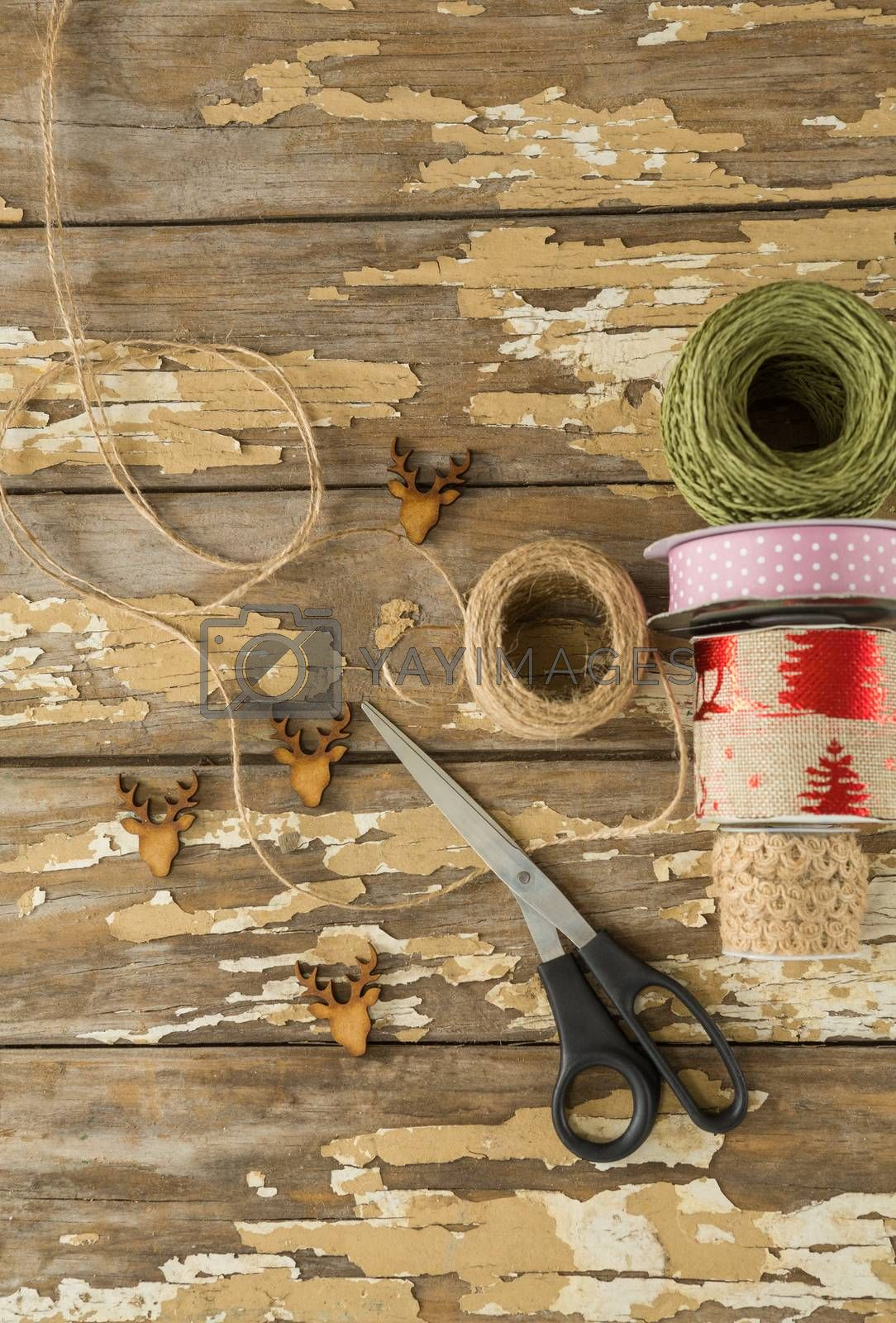 Ribbon roll, scissors and jute rope on wooden table by Wavebreakmedia