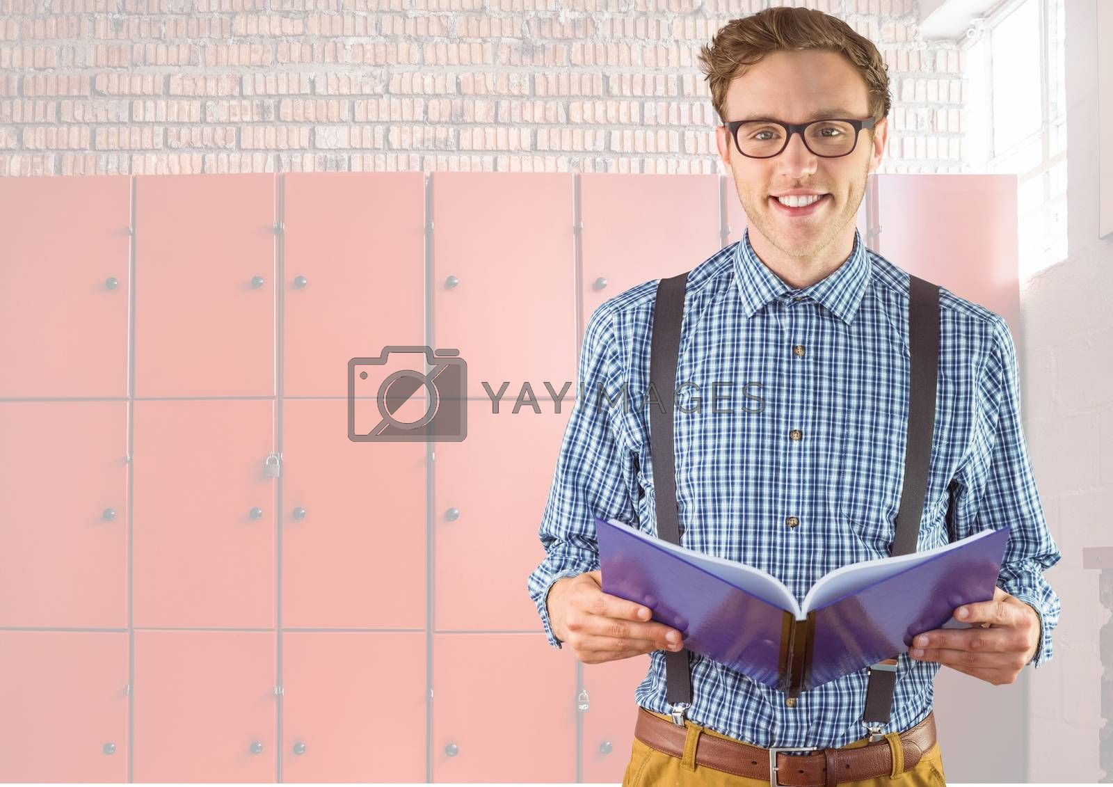 male student holding book in front of lockers by Wavebreakmedia