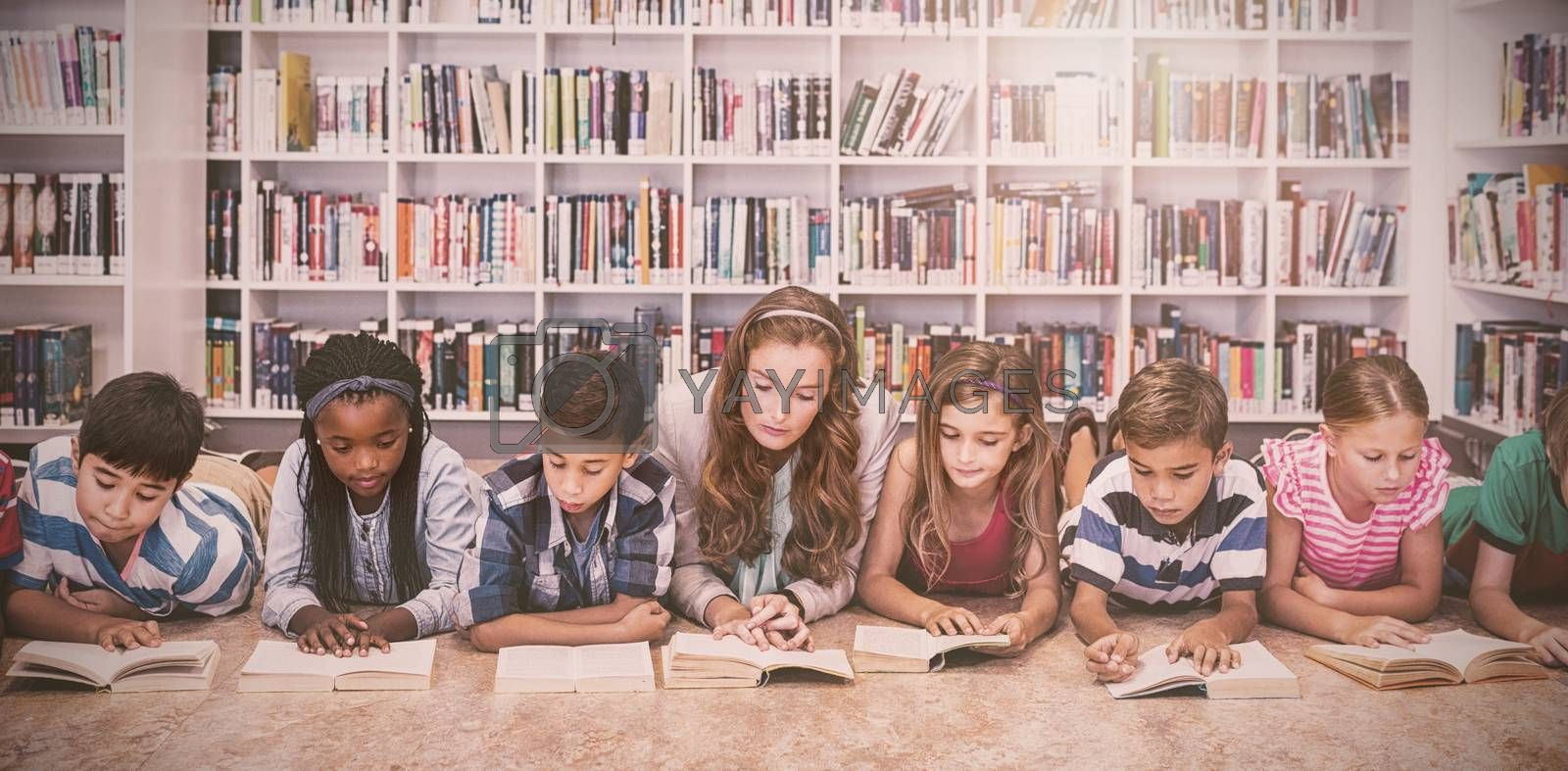 Teacher reading books to her students by Wavebreakmedia