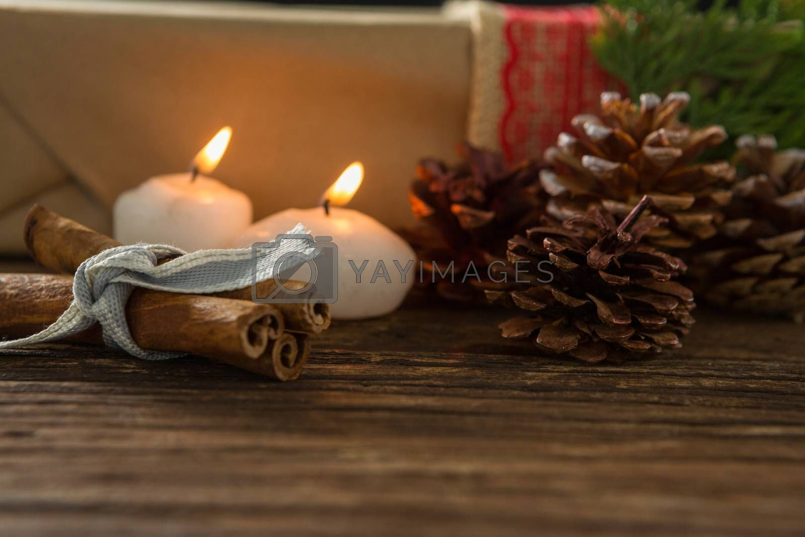 Illuminated candle with pine cones and cinnamon sticks by Wavebreakmedia