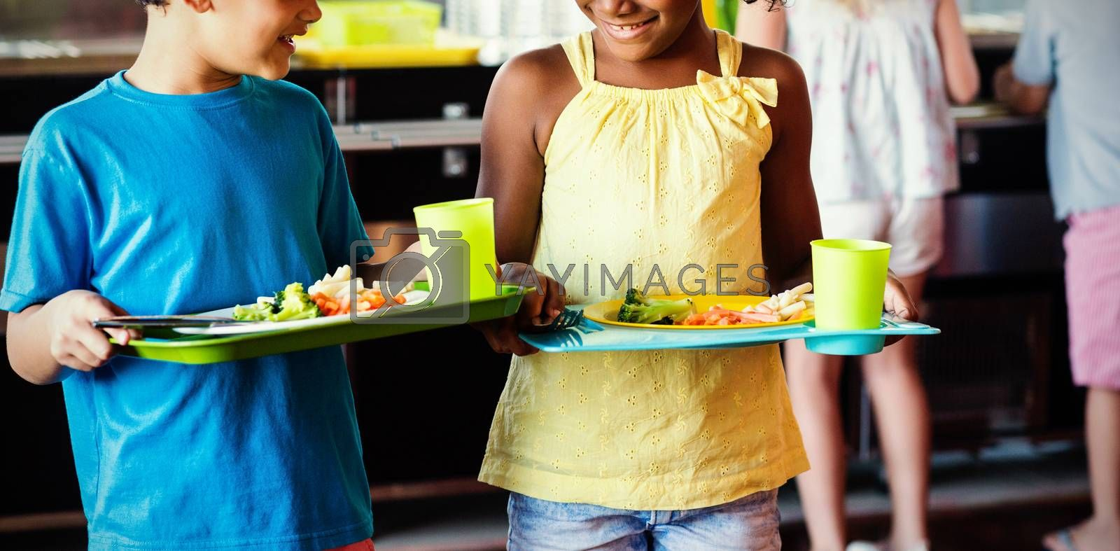 Children holding food tray in canteen by Wavebreakmedia