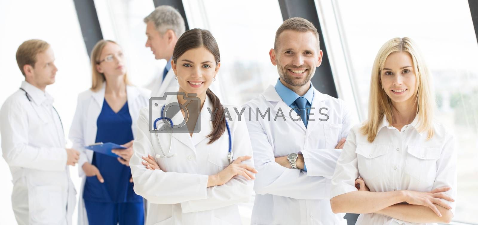 Team of medical professionals looking at camera, smiling, arms crossed