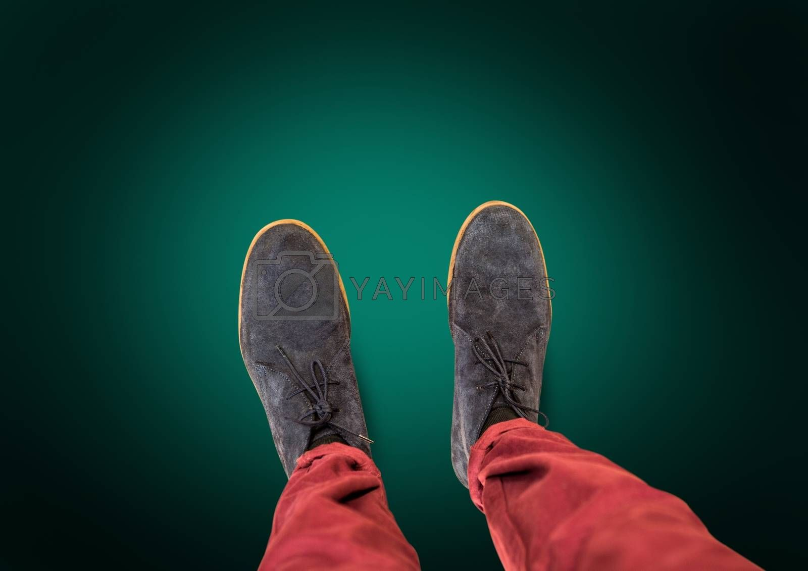Grey shoes on feet with green background by Wavebreakmedia